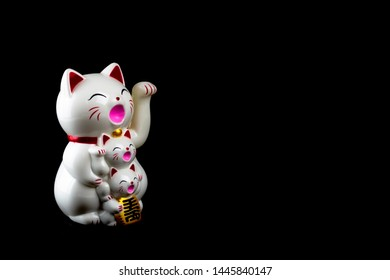 Lucky cat or Japanese triplet Maneki Neko on composition copy space isolated on black background for wishing good luck in business concept