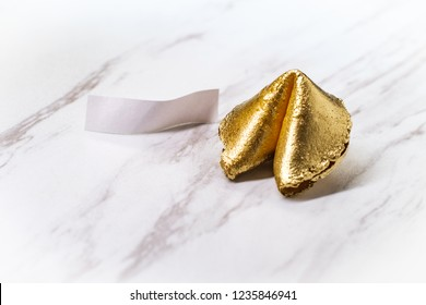 Lucky charm golden fortune cookie on marble table concept