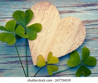Lucky clovers with an old wooden heart on a blue vintage wood background