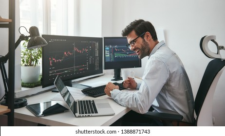 Lucky day. Happy young businessman or trader in formalwear and eyeglasses using laptop and smiling while sitting in his modern office