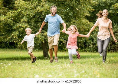 Lucky family with two kids togehter in spring at the park