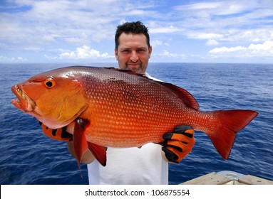 lucky  fisherman holding a beautiful red snapper