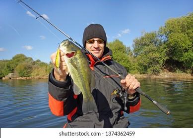 Lucky fisherman holding a big bass fish. Freshwater fishing, lure fishing, boat fishing