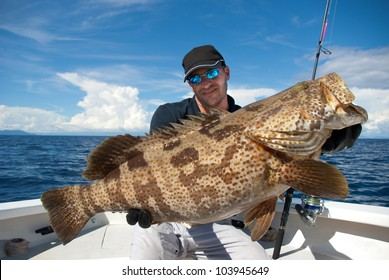 lucky  fisherman holding a big grouper