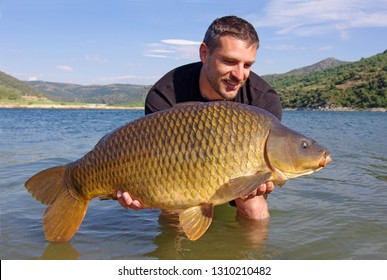 lucky fisherman holding a giant common carp. Freshwater fishing