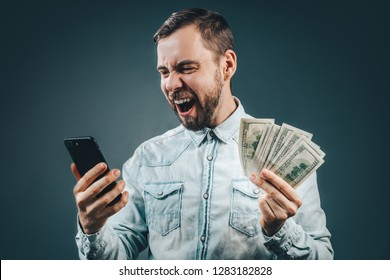 Lucky guy celebrating victory after making bets using gambling mobile application on his mobile phone. Casually dressed bearded business man holding ward of cash in hands.