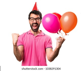 Lucky handsome young man holding balloons over isolated white background