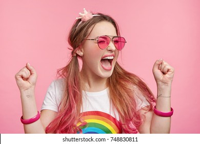 Lucky happy female model rejoices her victory on beauty contest, gets good prize, clenches fists with joy, screams happilly, isolated over pink background. Overjoyed young stylish female winner