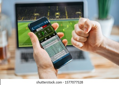 Lucky man celebrating money win. Male fan watching football play online broadcast on his laptop, cheering for his favorite team making bets at bookmaker's website.