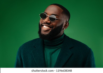 Lucky man. Style. Handsome Afro American guy in green jacket and sun glasses is looking at camera and smiling, on a green background