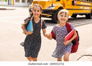 Lucky to meet each other. Cheerful smart schoolgirls. Happy schoolgirls outdoors. Small schoolgirls wear school uniform. Cute schoolgirls looking charming. Ending of school year.
