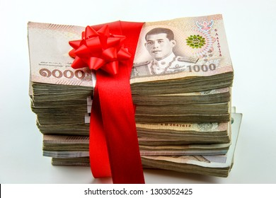 Lucky money gift : stack of 1 million Thai baht wrapped by red satin ribbon bow