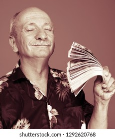 Lucky old man holding dollar bills on a gray background