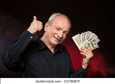 Lucky old man holding group of dollar bills and show OK sign