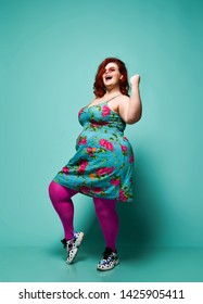 Lucky plus-size lady overweight woman in sunglasses and colorful clothes shows Yes sign gesture with her arm on mint background with free text copy space top