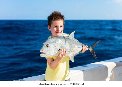 Lucky teenage boy holding fish on boat deck