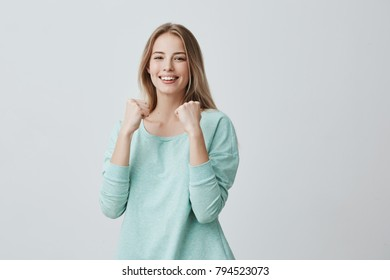 Lucky young female employee rejoicing success at work, smiling broadly, keeping fists clenched. Beautiful blonde girl in light blue sweater feeling happy and excited posing against gray background