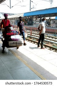 Ludhiana, punjab, india, 14th june 2020 : coolie (porter) is carrying the language of passengers at railway platform