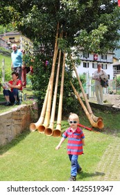 Ludiano - Switzerland / June 15, 2019. Swiss Folk Music Festival. Mother sends her son to call the alphorn players to stop eating and drinking, as the music must start.
