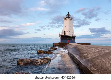 The Ludington North Breakwater Pier Lighthouse rises above Lake Michigan with an early morning sky.