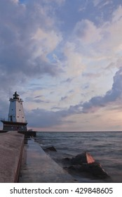 the Ludington Pierhead Light stands at the end of the Ludington Pier at Sunset against a puffy cloud sky and Lake Michigan