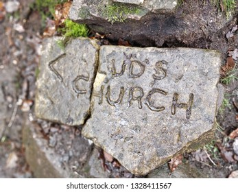 Lud's Church sign on rock at entrance to Lud's Church geological landmark in woods near Gradbach in the Peak District, UK.