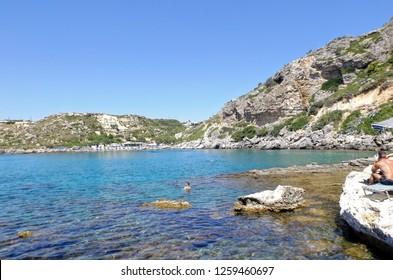 Ludzie pływający i opalając się na kamienistej plaży. Rodos Grecja