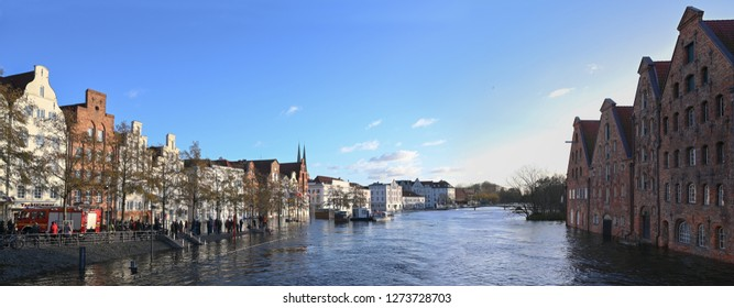 LUEBECK, GERMANY, JANUARY 2, 2019:  Panoramic view, River Trave with high water in the historic old town of Luebeck, Germany, blue sky, copy space