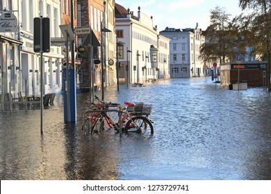 LUEBECK, GERMANY, JANUARY 2, 2019:  bicycles in the flood of the river Trave with high water in the historic old town of Luebeck, Germany, blue sky, copy space, selected focus