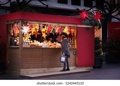 LUEBECK, GERMANY - NOVEMBER 26, 2018: Woman stands in front of a sales booth at the christmas market to buy gifts or illuminating decoration