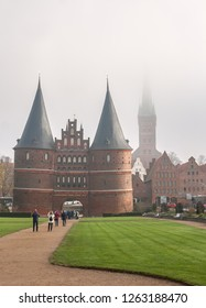 LUEBECK, Germany - November 7, 2018: Holsten Gate (Holstentor), city gate ( UNESCO World Heritage Site) and St. Petry zu Luebeck  in fog.