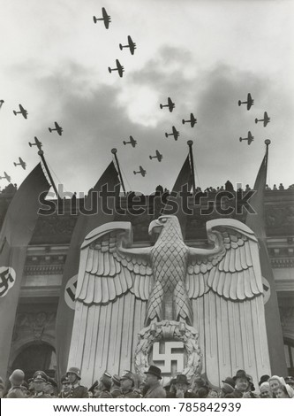 Luftwaffe Fly-By in honor of Hitlers birthday in Charlottenburg, Berlin, April 20, 1939. On the building is a sculpture of a Nazi German eagle and banners with swastikas
