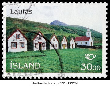 LUGA, RUSSIA - FEBRUARY 13, 2019: A stamp printed by ICELAND shows view of the turf houses and Church at Laufas dedicated to the Apostle Paul in Catholicism, North Iceland, circa 1993