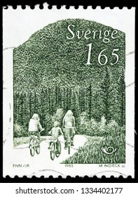 LUGA, RUSSIA - FEBRUARY 17, 2019: A stamp printed by SWEDEN shows cyclists family rides bicycles against Swedish landscape, circa 1983