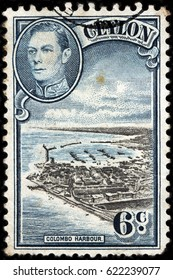LUGA, RUSSIA - FEBRUARY 7, 2017: A stamp printed by CEYLON shows image portrait of King George VI against beautiful view of Colombo harbor. Colombo is largest city of Sri Lanka, circa 1938.