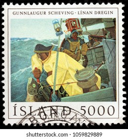 LUGA, RUSSIA - JANUARY 16, 2018: A stamp printed by ICELAND shows painting of Gunnlaugur Scheving. Fishermen on the Icelandic fishing boat, circa 1981