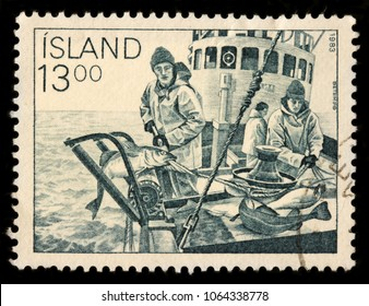 LUGA, RUSSIA - JANUARY 16, 2018: A stamp printed by ICELAND shows fishermen on the Icelandic fishing boat, circa 1983