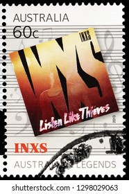 LUGA, RUSSIA - JANUARY 24, 2019:  A stamp printed by AUSTRALIA shows the cover of fifth studio album by the Australian rock band INXS - Listen Like Thieves, circa 2013.