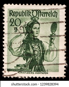 LUGA, RUSSIA - JANUARY 31, 2018: A stamp printed by AUSTRIA shows beautiful woman in national dress from Montafon - valley in the federal state of Vorarlberg, circa 1948