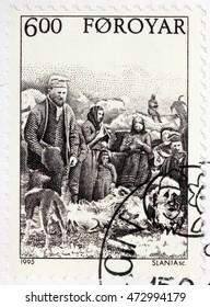 LUGA, RUSSIA - JUNE 25, 2016: A stamp printed by FAROE ISLANDS shows Faroese peasants fleecing sheep in farm, circa 1995.
