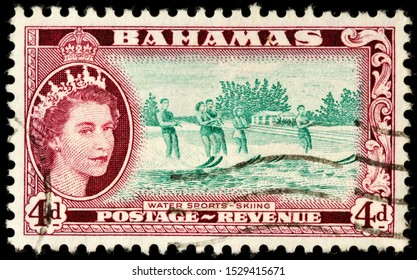 LUGA, RUSSIA - OCTOBER 05, 2019: A stamp printed by BAHAMAS shows image portrait of Queen Elizabeth II against view of the Bahamas beach with water skiers, circa 1954.