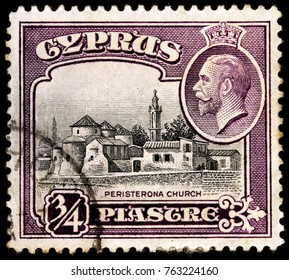 LUGA, RUSSIA - OCTOBER 17, 2017: A stamp printed by CYPRUS shows image portrait of King George V and view of the Church of St. Barnabas and St. Hilarion, Peristerona, circa 1934