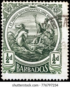 LUGA, RUSSIA - OCTOBER 17, 2017: A stamp printed by BARBADOS shows image portrait of George V, King of England, riding on a chariot across the sea and holding a trident, circa 1925