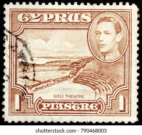 LUGA, RUSSIA - OCTOBER 17, 2017: A stamp printed by CYPRUS shows portrait of King George VI and view of Soli Theater. Soli or Soloi is an ancient Greek city in the island of Cyprus, circa 1938