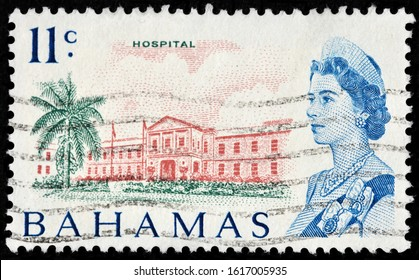 LUGA, RUSSIA - OCTOBER 5, 2019: A stamp printed by BAHAMAS shows image portrait of Queen Elizabeth II against view of Princess Margaret Hospital in Nassau City, New Providence, circa 1967