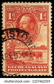 LUGA, RUSSIA - OCTOBER 7, 2017: A stamp printed by BECHUANALAND shows image portrait of King George V against beautiful view of baobab tree and cattle drinking, circa 1932