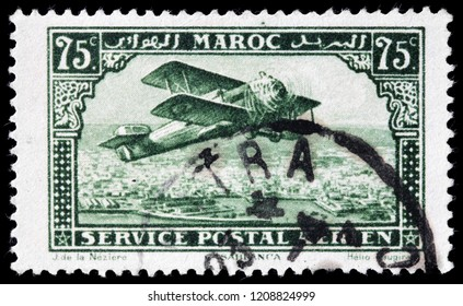 LUGA, RUSSIA - SEPTEMBER 12, 2018: A stamp printed by MOROCCO shows biplane over Casablanca - the largest city in Morocco, circa 1926