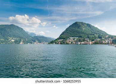 Lugano city, Canton Ticino, Switzerland. Lugano lakefront and Lugano lake with the San Salvatore mountain in summer. On the left, the city of Campione d'Italia is visible in the background