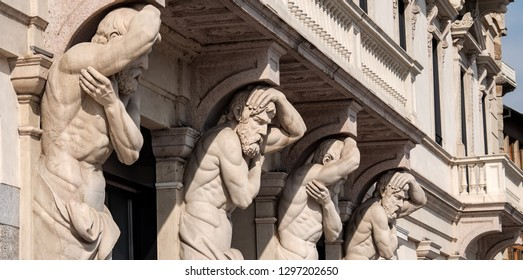 Lugano, Switzerland, 03/09/2018: Four male sculptures on a house facade in the city of  Lake Lugano