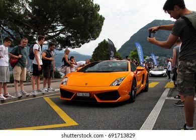 Lugano, Switzerland - 05.07.17: Lamborghini Gallardo Superleggera supercar arriving at Cars&Coffee event held on Lugano lakeside alleyway. A British McLaren 675LT is following this orange sports car.